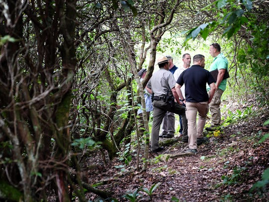 National Park Service and other federal Investigators investigate a crime scene on the Blue Ridge Parkway in July 2018 where a woman's body was found. The park in North Carolina and Virginia receives 14.7 million visitors a year and had 20 fatalities in 2018. It will send up to three law enforcement rangers on details to the U.S.-Mexican border in the next six months.