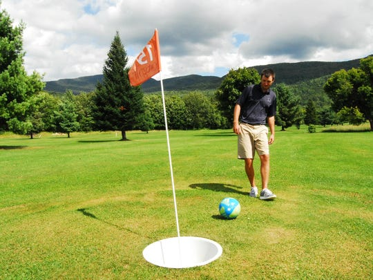 Colin O'Brien attempts a putt for par while demonstrating the play of FootGolf at West Bolton Golf Club on Wednesday. The new sport uses standard soccer balls on a specially-designed course alongside the regular golf holes.