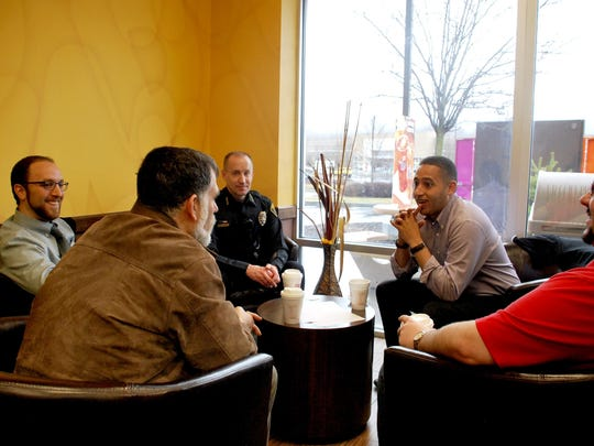 Ithaca police Chief John Barber, center, and Ithaca Mayor Svante Myrick, second from right, speak with local residents at a Dunkin' Donuts in April 2015 as part of a community outreach.
