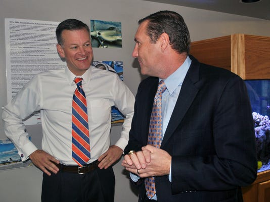 FILE - In this Monday, Nov. 27, 2017 file photo, University of Florida athletic director Scott Stricklin, left, smiles as he talks to Florida's new NCAA college football coach Dan Mullen after Mullen arrived at the airport in Gainesville, Fla. Making the home-run hire seems to be more difficult than ever for schools searching for a new head football coach. Scott Stricklin moved quickly to hire one of the few proven coaches available this year in Dan Mullen, who during nine years at Mississippi State had become maybe the most successful coach the program has had. (AP Photo/Mark Long, File)