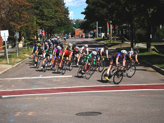The peleton, or lead pack, of the Men 2 category race turns from Bank Street onto Pine Street during Monday's Dealer.com Burlington Criterium.