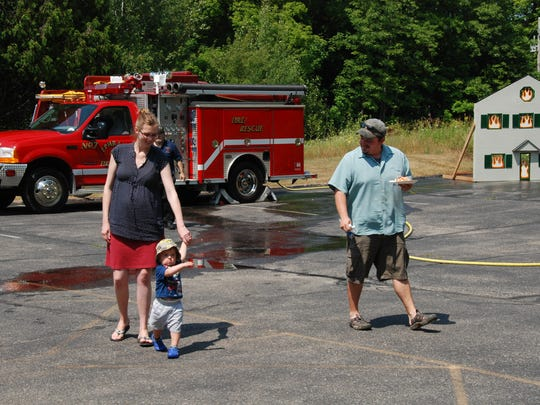 Ephraim residents, Brent and Erin Bristol, show their son, Henry, around the Ephraim Fire Station during the annual open house.