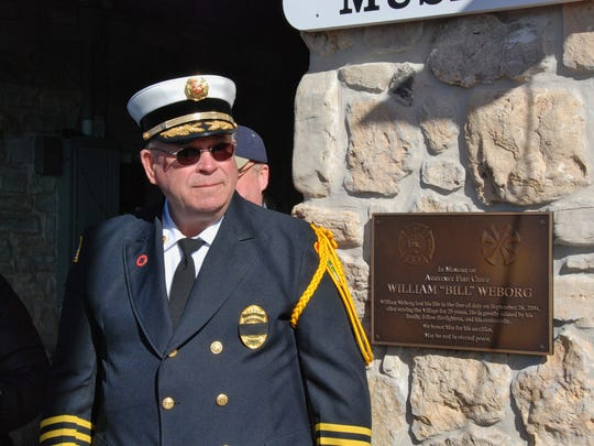 Ephraim Fire Chief Niles Weborg stands by a plaque honoring his son, Bill, who died in the line of duty as an Ephraim firefighter 10 years ago.