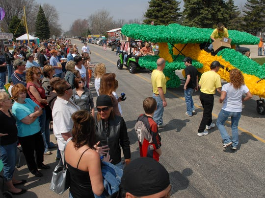 """Spectators watch as a plane with """"Adair Bar"""" on the side goes through Adair during the 2008 Suckerfest parade. The parade makes a big deal about a fish that few hold in high regard."""