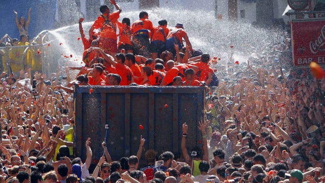 """Crowds of people throw tomatoes at each other, during the annual """"tomatina"""" tomato fight fiesta, in the village of Bunol, 50 kilometers outside Valencia, Spain, Wednesday, Aug. 27, 2014."""