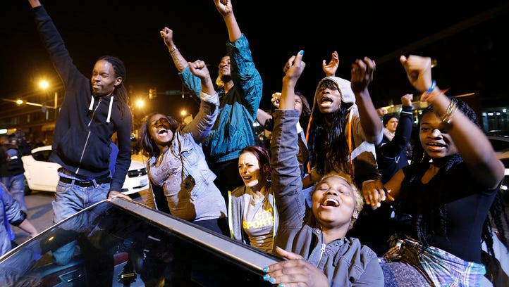 Demonstrators celebrate the announcement of six officers