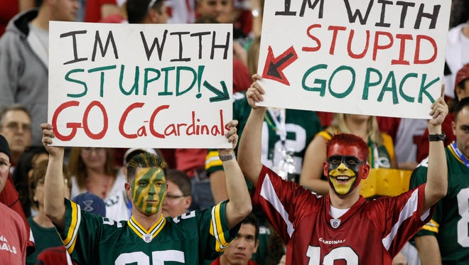 Packers fan Nick Wagner and Cardinals fan David Ricardo hold up signs for their teams during a 2010 playoff game in Glendale.