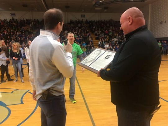 Associate principals Jeff Van Lannen, left, and Brian Matz, right, surprise Principal Rod Bohm, middle, by announcing his selection to Green Bay Southwest High School's Distinguished Alumni honor wall during an assembly in the school gym Friday.