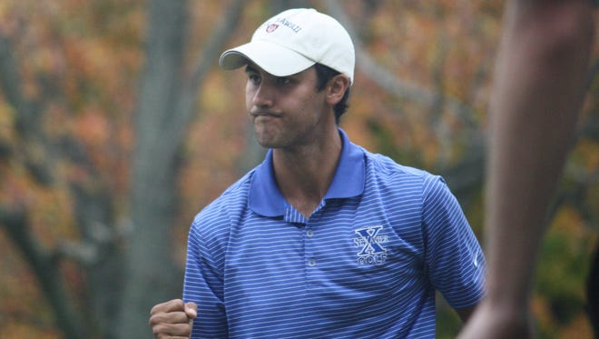 St. Xavier senior Kirran Magowan celebrates sinking a birdie putt on 18 to help the Bombers secure a Division I state golf championship on Oct. 24 on the scarlet course at the Ohio State University Golf Club.