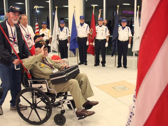 World War II veteran Bob McDonald salutes the flag as he is escorted by Ned Herrmann to the security gate during an Honor Flight. There's welcome home parties Saturday night in Naples and Fort Myers.