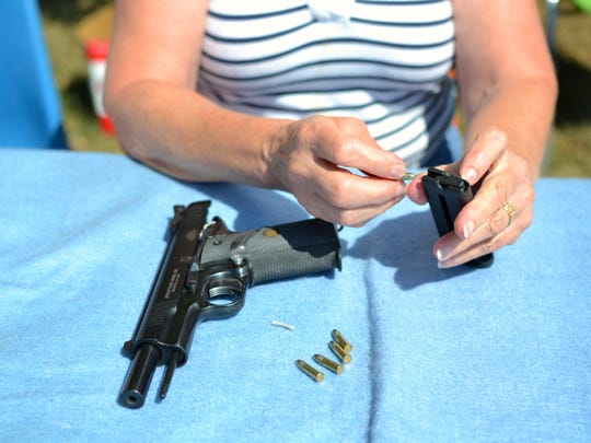 Susan Fassett, of Richmond, learns how to load a handgun.