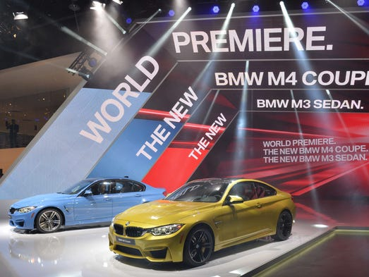 The BMW M4 coupe (right) and the M3 sedan are presented during the press preview at the North American International Auto Show in Detroit, Michigan.