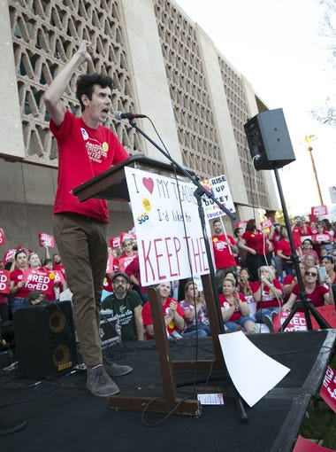 Noah Karvelis, (center) a teacher and leader in Arizona Educators United, speaks as Dylan Wegela, also a teacher and leader in Arizona Educators United, listens as they list their demands for Arizona leaders during a #RedForEd rally at the Arizona State Capitol in Phoenix on Wednesday, March 28, 2018.