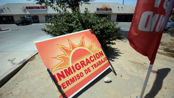 A curbside sign promotes immigration services outside Silvia Chapa's business on Harrison Street in Coachella, California.