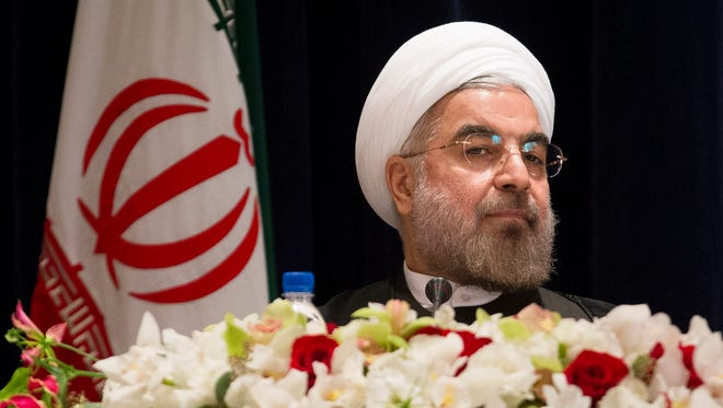 Iranian President Hassan Rouhani takes his chair before a news conference at the Millennium Hotel in midtown Manhattan, Friday, Sept. 27, 2013, in New York.