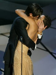 Adrien Brody, left, plants a kiss on Halle Berry.