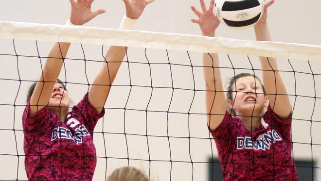 Kari Dominguez, left, and Elena Williams team on a Lady Cat block during Saturday's District 3-5A win over Alamogordo.