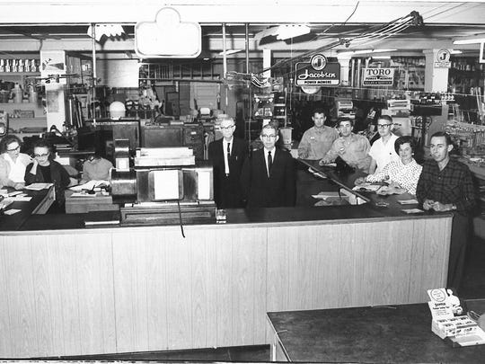 """The date listed on this file photo from Feb. 7, 1964. According to the original cutline that ran with the photo: """"At Noble Hardware Co., 915 to 917 Indiana, every corner stands out with quality while this office-counter at the center of the store stands out with friendly service. The counter is maintained in old-fashioned friendly style that is a trademark of Noble's. From left are Mrs. Ihla Spence, Mrs. M.E. Mackechney, Mrs. Maxine Sanders, Lawson Junell, Jimmy Maxwell, Curtis Brown, Larry Williams, Charles Hutson, Mrs. Alys McDaniel and Joe Stevenson."""""""