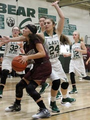 Tularosa's Ember Cervantes, center, drives toward the basket while being defended by Cloudcroft's Marisol Paulik (24).
