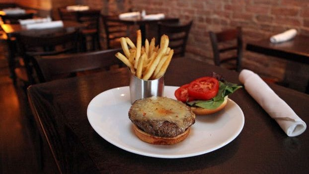 The Mill Burger, with house rub, New York aged cheddar, heirloom tomato and cracked pepper and sea salt fries, is photographed at The Mill, Sept. 12, 2013 in Hastings-on-Hudson. The gastropub offers craft beers and cocktails, and a farm-to-table menu. ( Tania Savayan / The Journal  News )