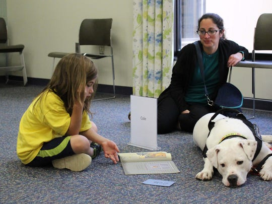 Crosby DiCicco, 7, reads to therapy dog Cole as mom,