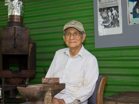 """Master Blacksmith Joaquin """"Jack"""" Lujan sits near his forge and anvil where he hangs newspaper clippings of him and his father working together as a reminder of where he learned his blacksmith skills from in this. April 2011 file photo."""