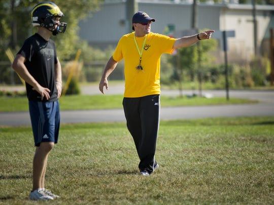 Coach Scott Barnhart talks with players during football