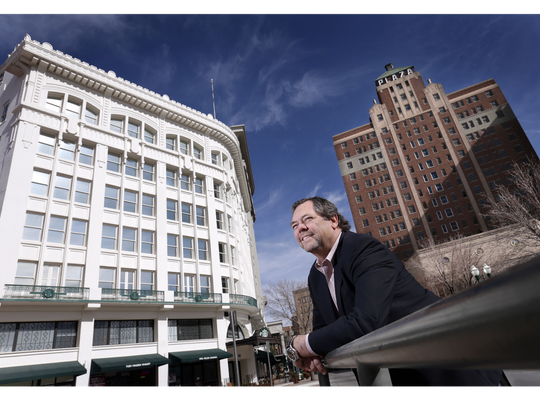 Paul Foster stands by two of his Downtown properties: the Plaza Hotel building, right, and the Centre Building.