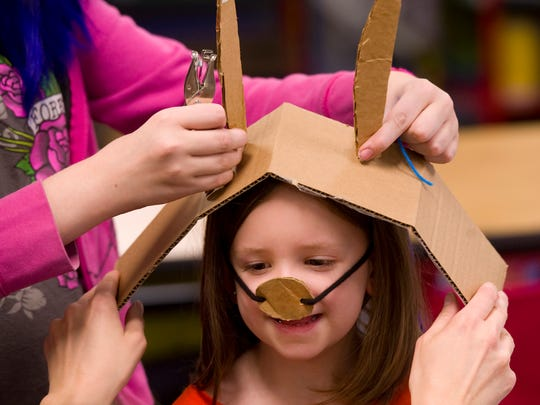 Averee Hufstedler gets a little help with her cardboard bunny ears from sixth-grader Angel Tines and art teacher Rachel Walker before the big parade at Delaware Elementary School Monday afternoon.
