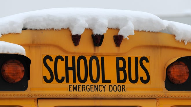 Indianapolis Public Schools buses sit covered in snow at a depot off of Massachusetts Avenue.