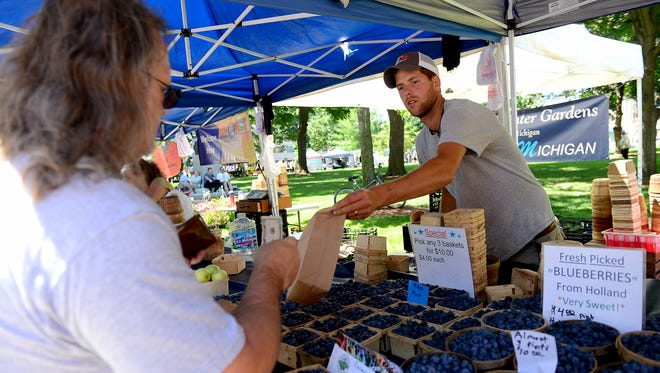 A patron picks up some fresh blueberries at the Diemer's Winter Gardens farm stand Thursday at the 10th-annual Farmers Market at the Capitol in Lansing.
