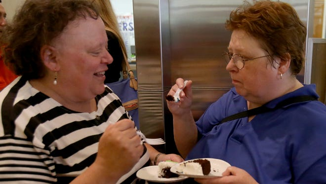 Eugenia Fernandez (left) and Theresa Hurn share a wedding cake June 25, 2014, after their ceremony inside the City-County Building in Indianapolis.
