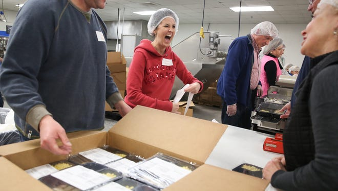 """Second from left, volunteer Christie Henry of Nashville, Tenn. shares a smile with other volunteers during the Second Harvest Food Bank's """"Feed the Need Sort and Pack."""""""