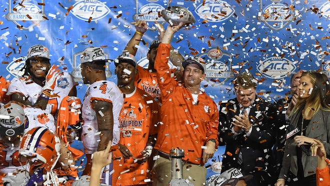 Clemson head coach Dabo Swinney holds the ACC Championship trophy after the Tigers 42-35 win over Virginia Tech at Camping World Stadium in Orlando on Saturday, December 3, 2016.