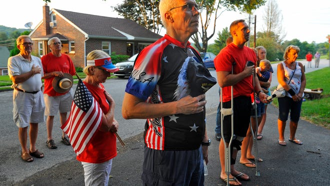 Neighbors Glenn Engler, center, and wife Linda, left, join Joshua Corney's family in front of their Glen Rock home for the playing of taps, Tuesday, July 4, 2017.  John A. Pavoncello photo