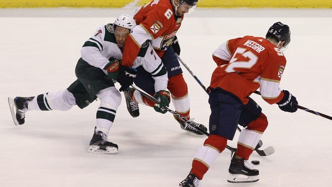 Minnesota Wild's Matt Cullen (7) and Florida Panthers' Alex Petrovic (6) battle for the puck as Panthers' MacKenzie Weegar (52) defends during the first period of an NHL hockey game, Friday, Dec. 22, 2017, in Sunrise, Fla. (AP Photo/Luis M. Alvarez)
