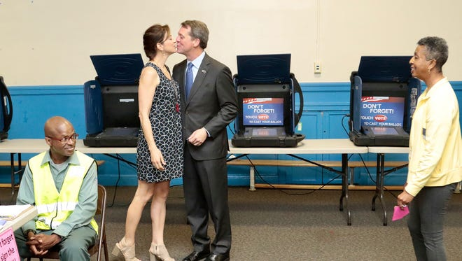 Democratic candidate for South Carolina governor James Smith kisses his wife, Kirkland Smith, after voting in the South Carolina Primary at AC Moore Elementary School, in Columbia, S.C., Tuesday, June 12, 2018.