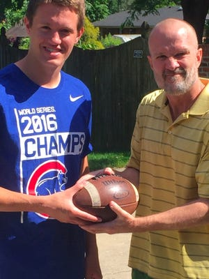 Gregg Doyel holds a football with Roncalli's Derek O'Connor. Doyel found the football at Play It Again Sports.