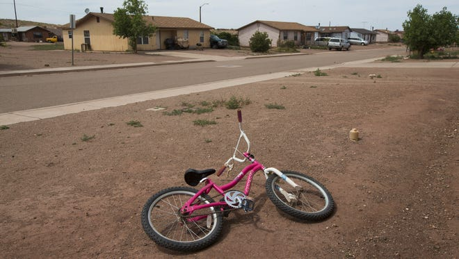 A bike lays in an unfinished front yard in Cameron, Ariz., in 2015. Residents of this Navajo Housing Authority development complain of poor construction.