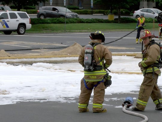 Firefighters stand by gasoline covered in foam and