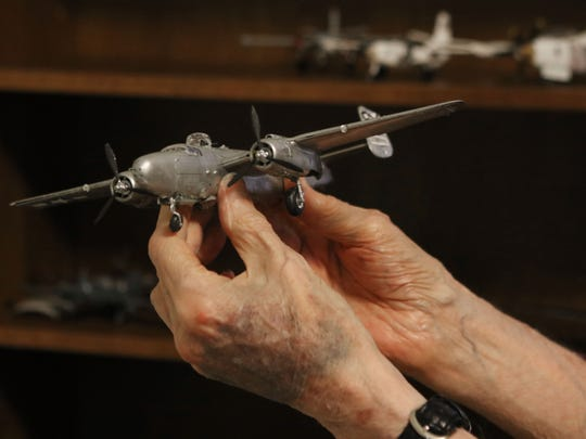 Allen Vrooman, 92, holds a model of a B-25 bomber he