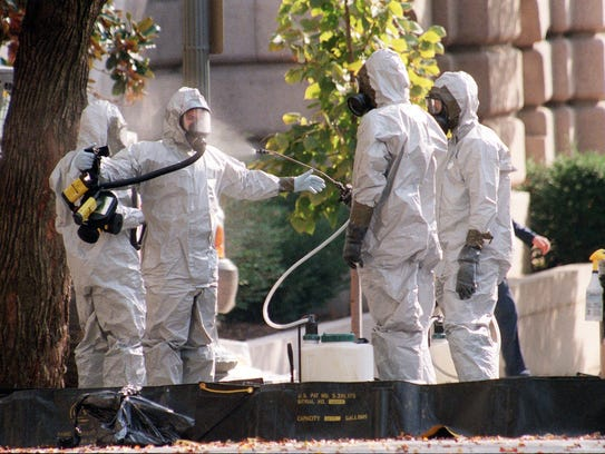 A hazardous materials unit worker is hosed down on