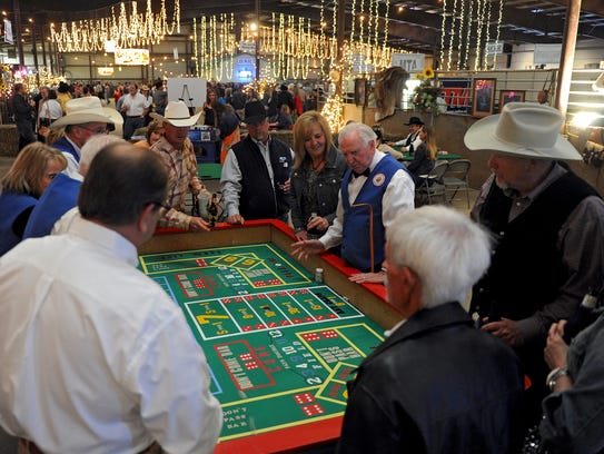 In this 2014 file photo, a group gathers around the craps table in the gaming and casino area of the Cattle Baron's Ball at the J.S. Bridwell Agricultral Center. The cancer fundraiser, which happens every two years, will be April 7.