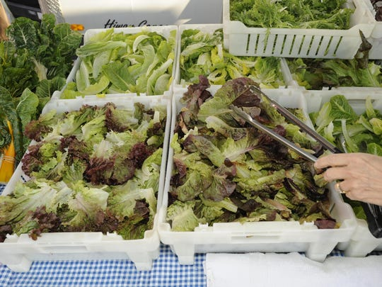 A customer shops for lettuce at the Oak Patch Vegetables booth during the Visalia Farmers Market on Saturday.