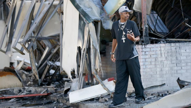 A man takes photos of the aftermath of last weekend's violence in the Sherman Park neighborhood.