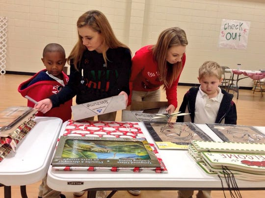 Pineville High juniors and Club Kid founders Michaela Triche (second from left) and Karlee Littleton help J.I. Barron Elementary kindergarteners Ja'Kayden Greene (left) and Adam Theriot shop for their families Thursday in the school's annual Santa Shop.