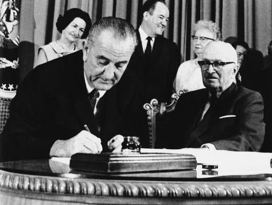 President Lyndon Johnson signs the Medicare Bill into