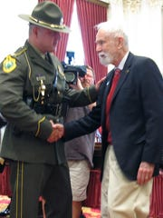 Peter Mason, center, shakes the hand of Col. Tom L'Esperance, head of the Vermont State Police, Friday, June 20, 2014 at the State House in Montpelier. Mason was honored for his role in the 1944 rescue of an airman injured in the crash of a B-24 bomber on Vermont's Camels Hump mountain. Mason, of Pasadena, Calif., and Rolland Lafayette, of Waterbury, Vt., are the only surviving rescuers of James Wilson, a 19-year-old Army airman who survived a crash and went on to became a lawyer in Colorado.
