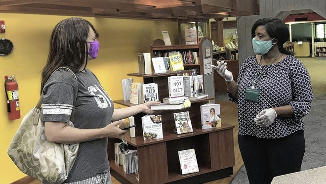 Jennifer Michelea (left) takes a book to check out from the Pickerington Public Library Main Branch on July 9 as Ashely Mensah, a library system customer service manager, offers assistance. The library reopened the doors to its two branches July 6.
