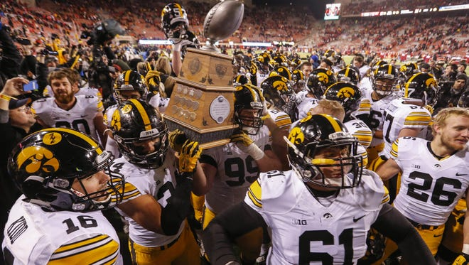 Members of the Iowa Hawkeye football team celebrate with the Heroes Trophy after beating Nebraska to finish the season at 12-0.